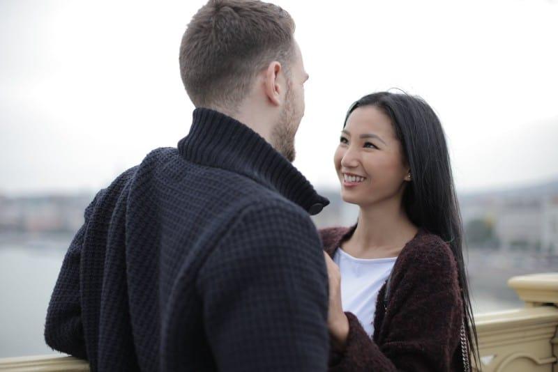 happy couple standing on bridge and making eye contact