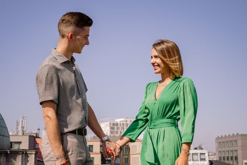 man and woman holding hands and standing on rooftop