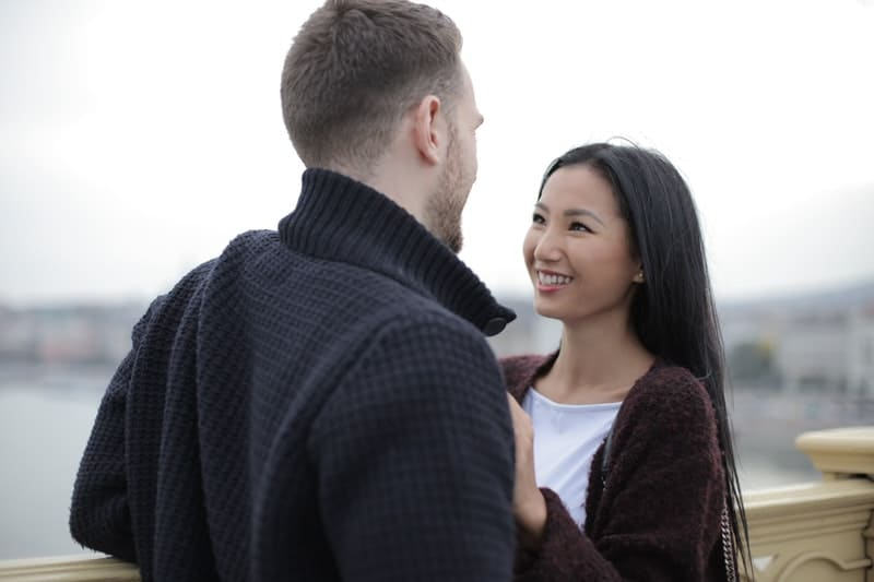 couple standing on the bridge talking to each other