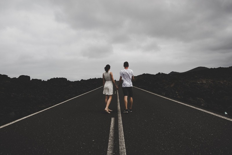 man and woman standing on the road and holding hands
