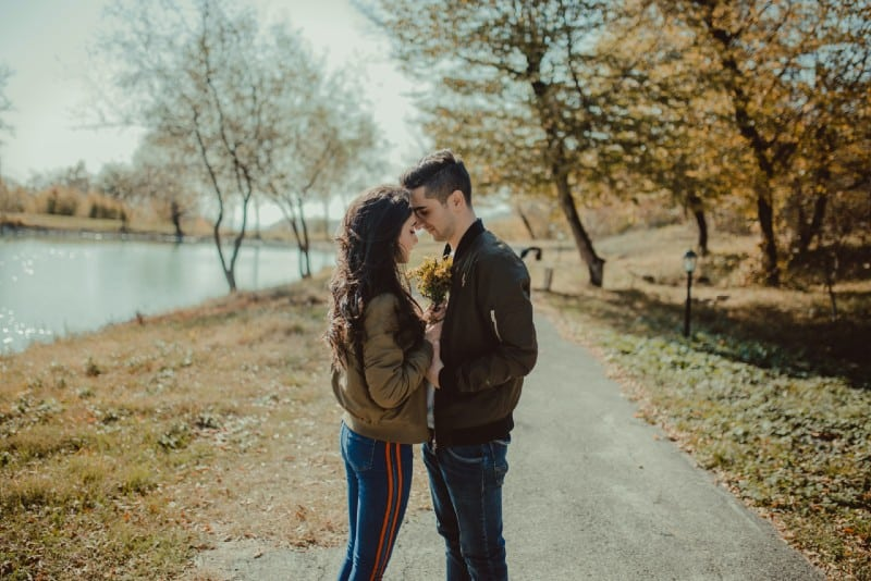 man and woman facing each other standing on footpath