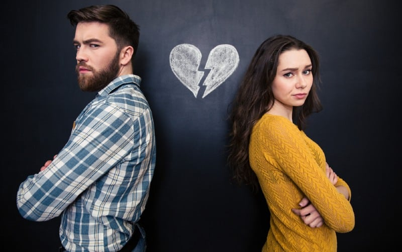 Unhappy young couple standing with arms crossed with background of chalkboard with drawn broken heart