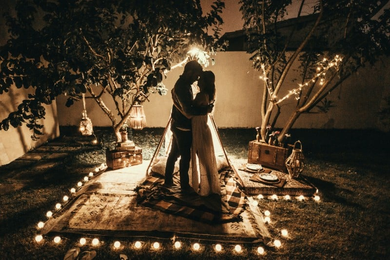man and woman hugging while surrounded by tealights