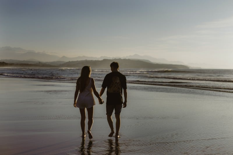 man and woman holding hands and walking on beach