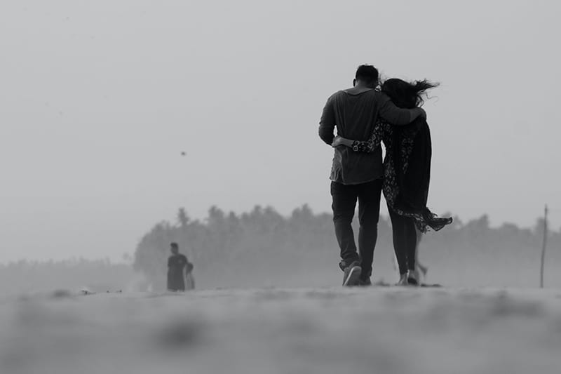 couple walking on ground while hugging each other
