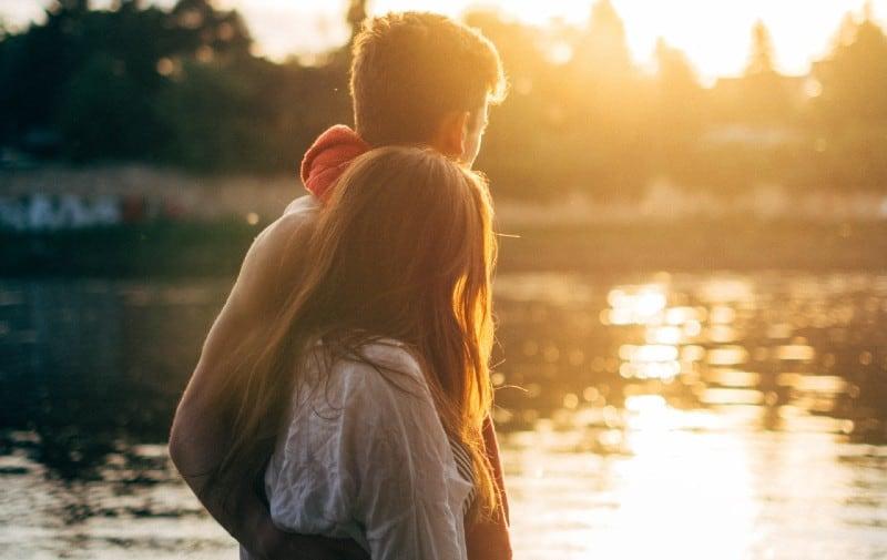 close-up-of couple walking on lake side watching sunset