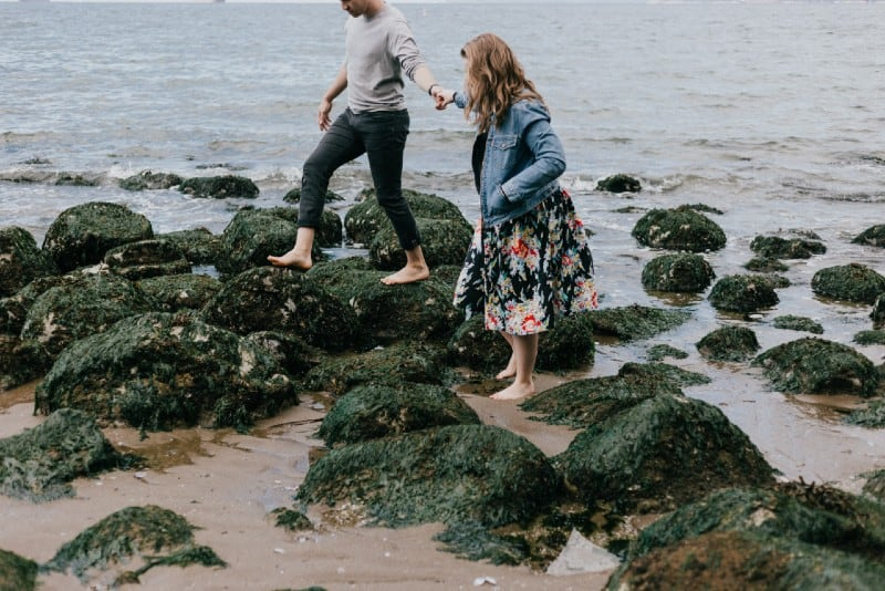 man and woman holding hands while stepping on rocks near sea