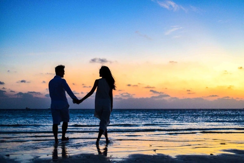 man and woman holding hands walking on seashore during golden hour