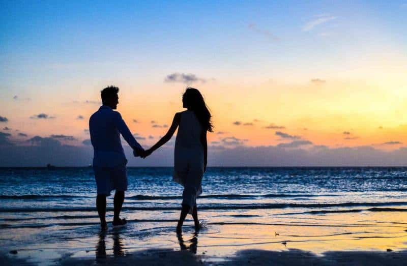 Romantic man and woman couple-walking on-the beach during sunset time