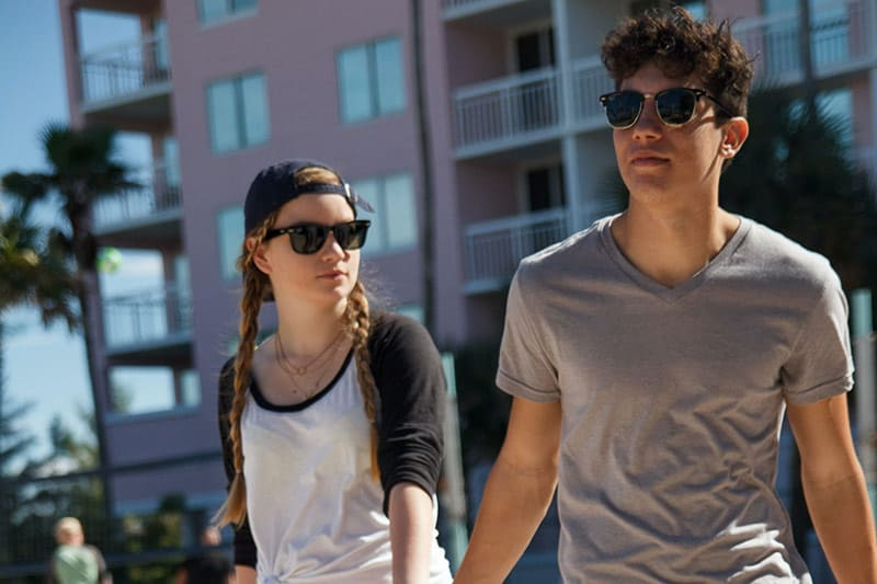 Couple walking by the beachside wearing shades