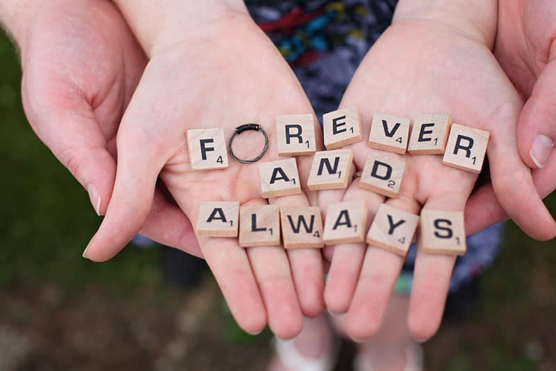 couple's hands with scrabble letters forming forever and always with a ring on O