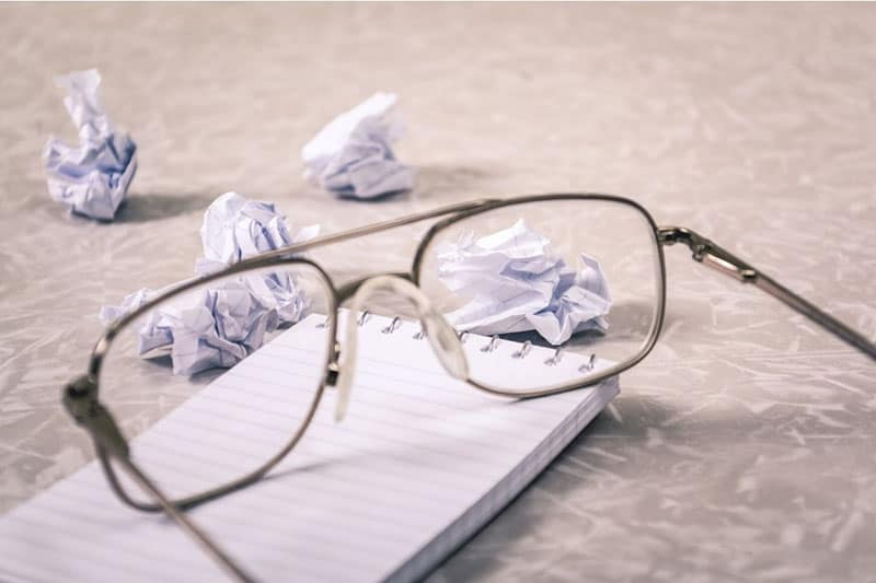 crumpled papers around a notebook and an eyeglasses