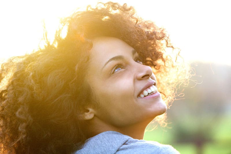 cute afro woman looking at sky