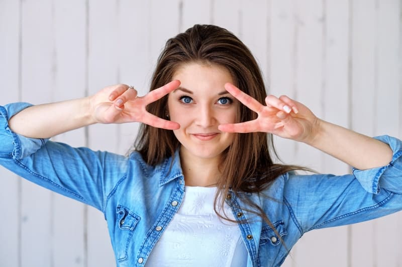 cute beautiful woman wearing blue and white top doing a hand sign