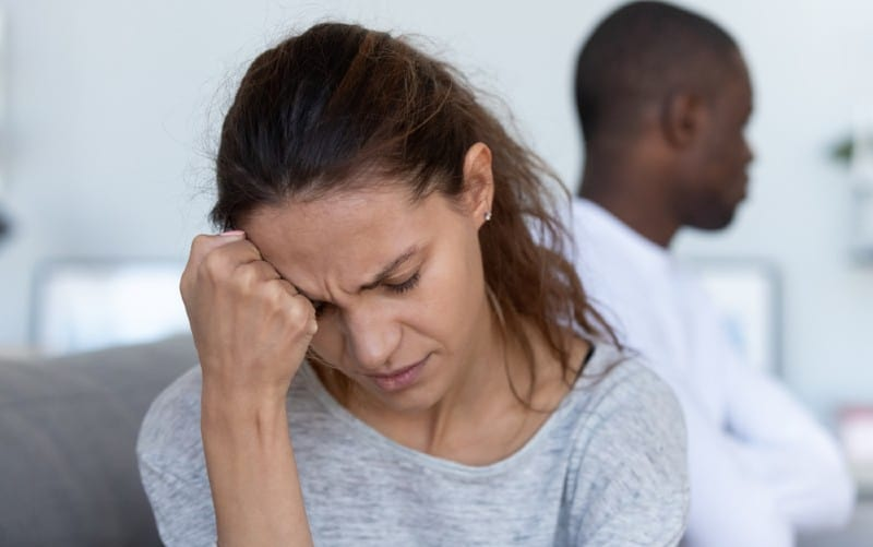 Depressed and sad young woman sitting near man
