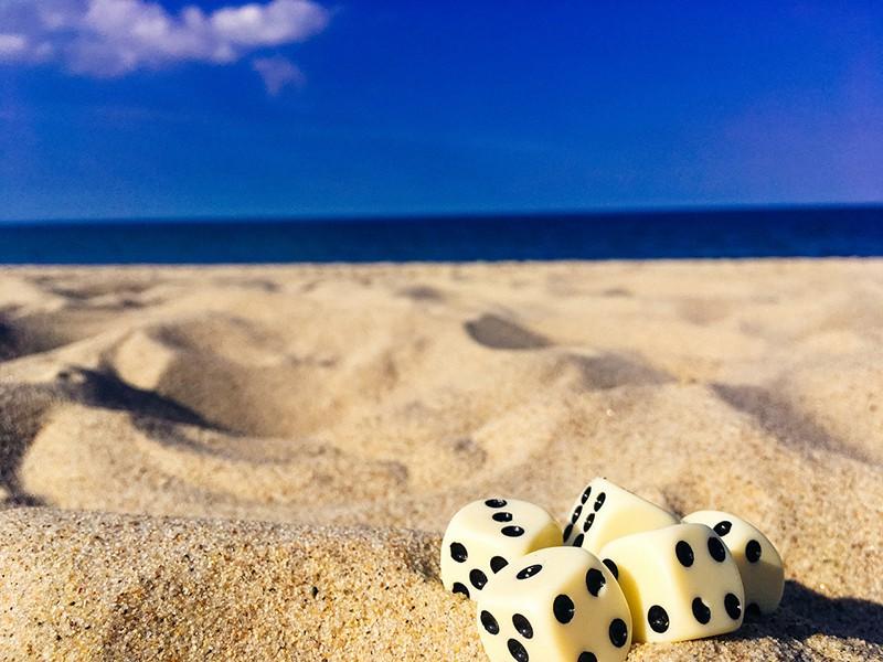 five dice on sand under blue sky
