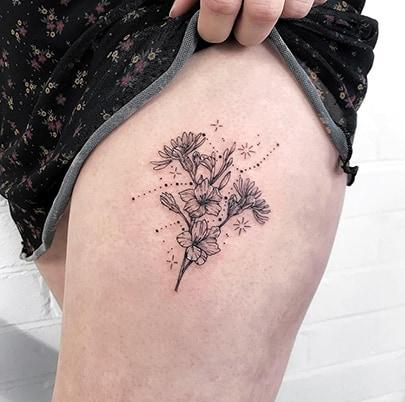 Floral Virgo constellation tattoo on the thigh