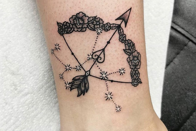 floral bow feathered arrow and sagittarius constellation tattoo on the anckle
