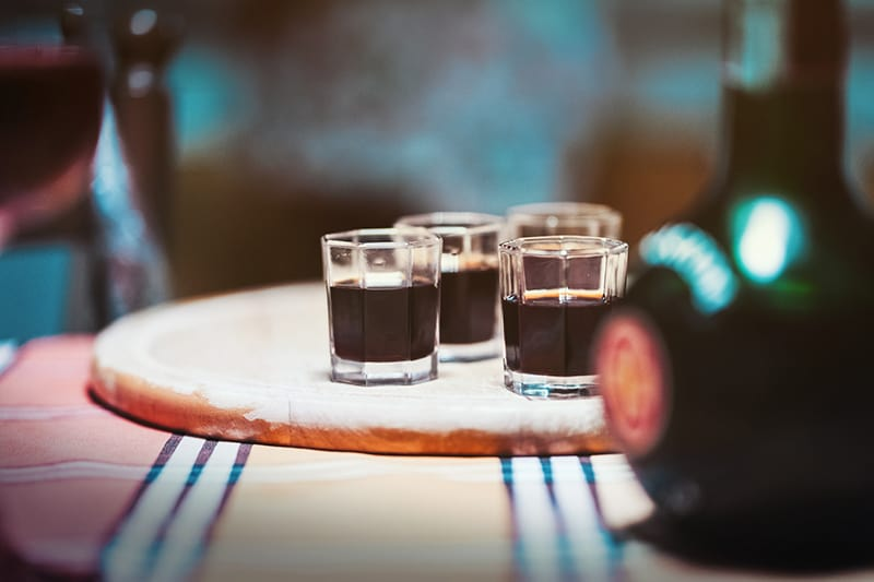 four clear drinking glasses on top of brown board