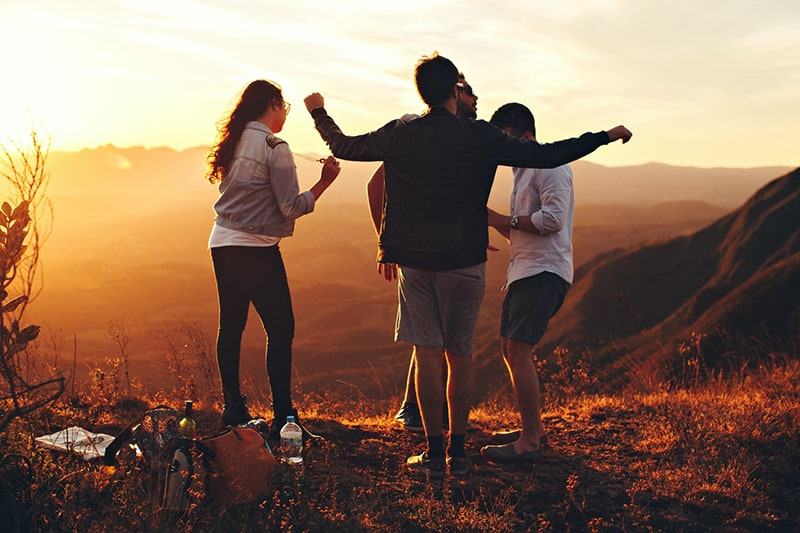 four person standing on the top of mountain