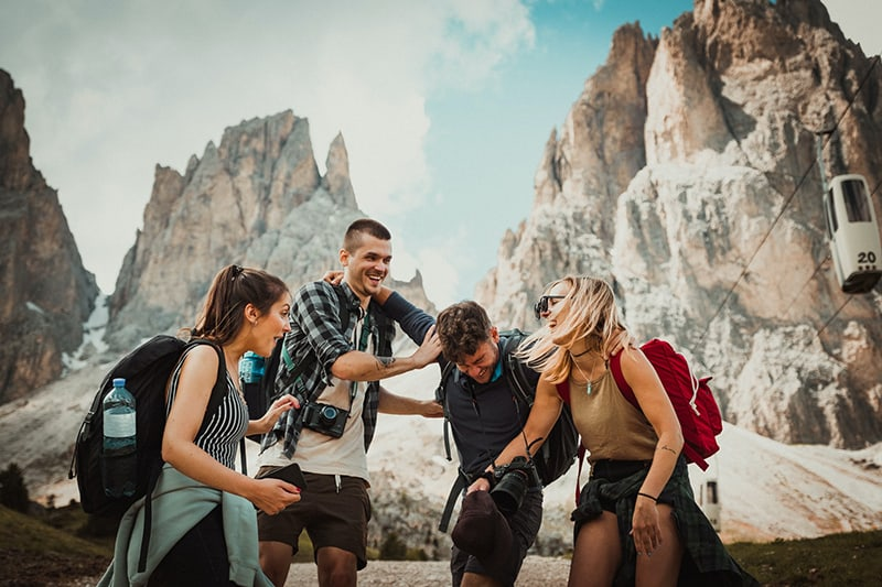 four persons laughing while hiking