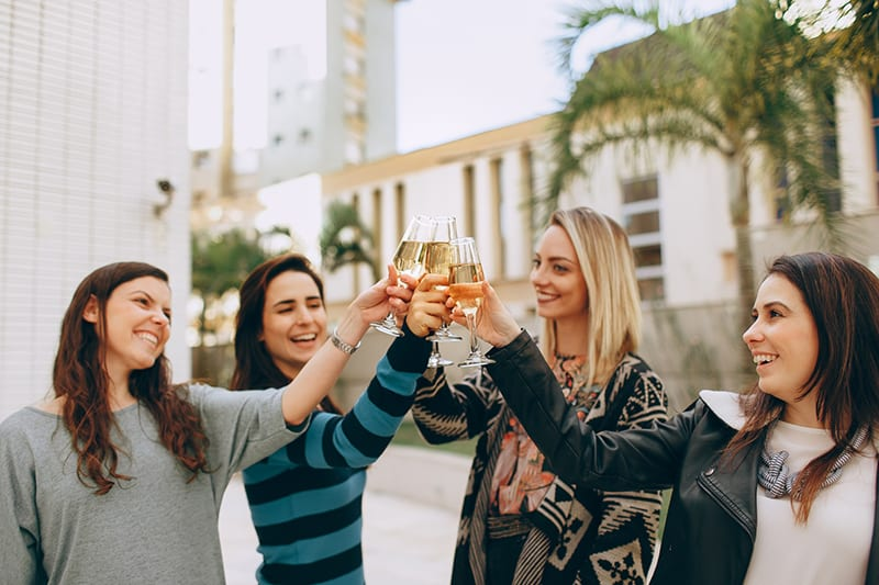 four women holding drinking glass while having a toast