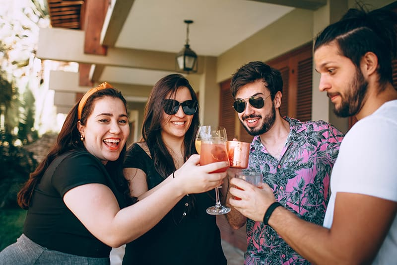 friends holding drinking glasses in back of house
