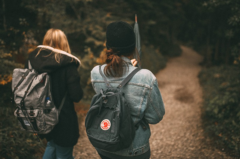 friends walking in the forest with backpack on their back
