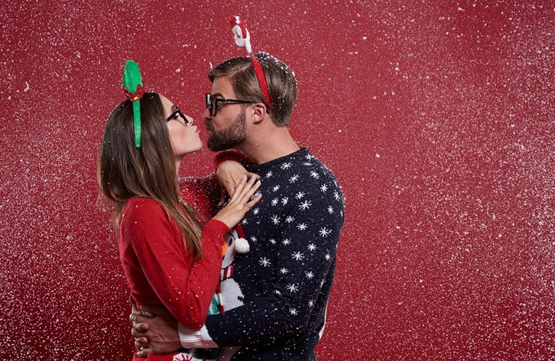 geeky couple kissing on christmas sweaters near red wall