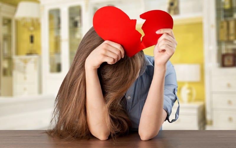 Sad lonely girl holding paper broken heart