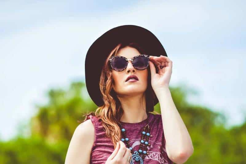 girl in pink tank top wearing black sun hat and black sunglasses