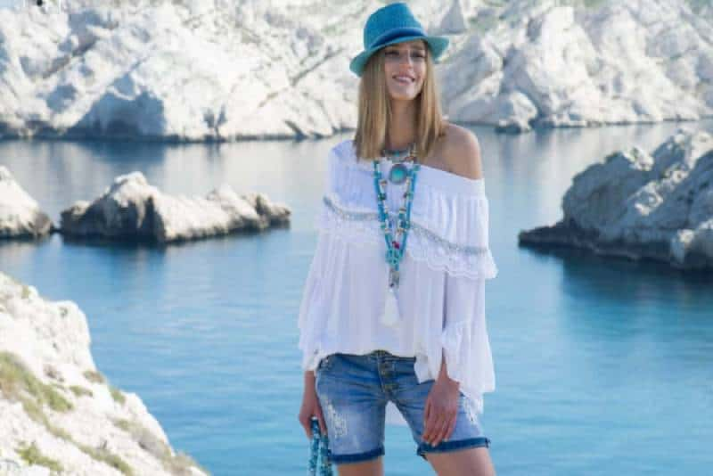 girl wearing white top and shorts while standing on a body of water