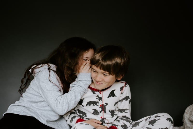 girl whispering into boy's ear while sitting indoor