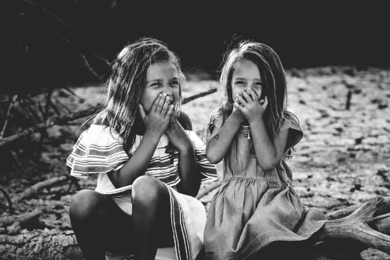 two girls closing their mouth and laughing