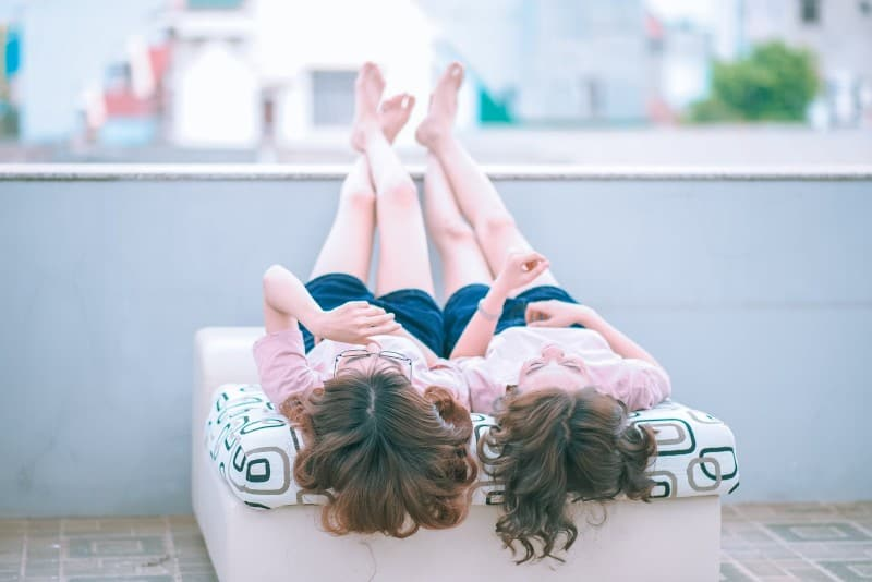 two girls in pink shirts lying on sofa while looking up