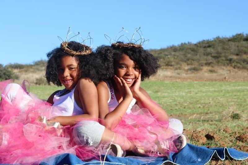 two girls wearing ballerina dress sitting on blanket