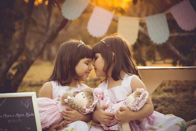 female twins playing with dolls outdoor