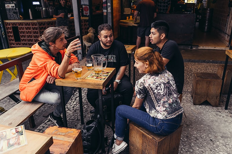 group of friends drinking while they sitting in tavern