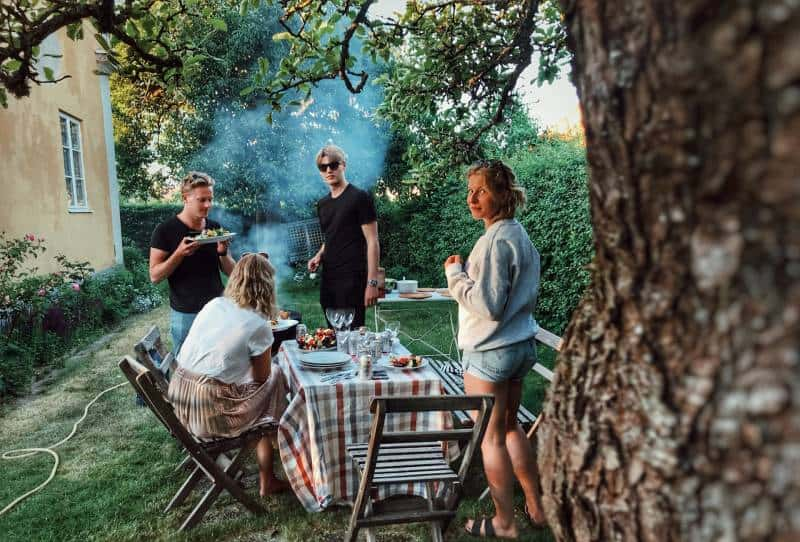 group of people barbecuing in garden