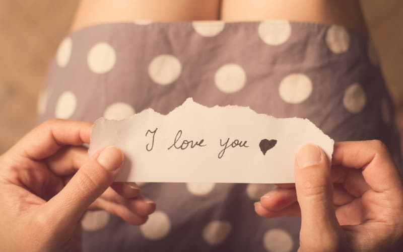 hands of a woman in dotten dress holding a paper with i love you message on it