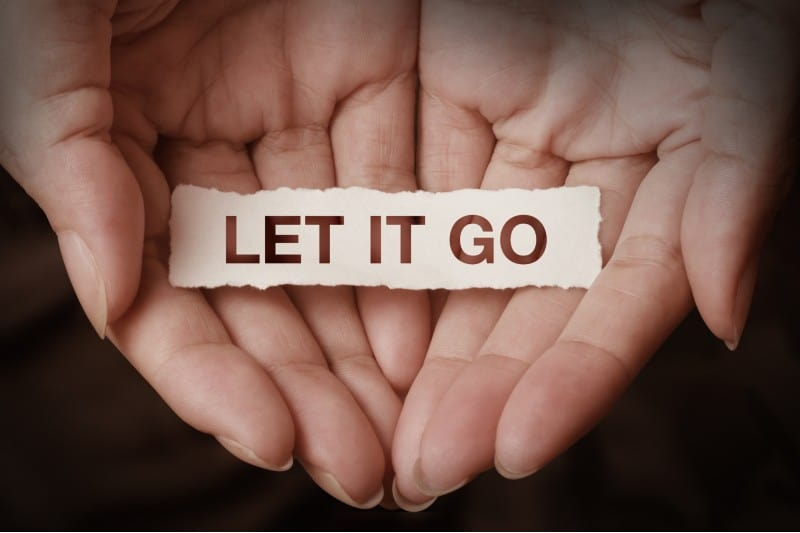 Hands holding let it go message written on paper