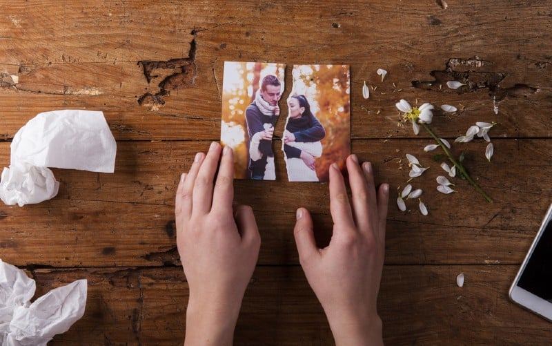 hands of a woman touching torn picture of a couple on a brown wooden table