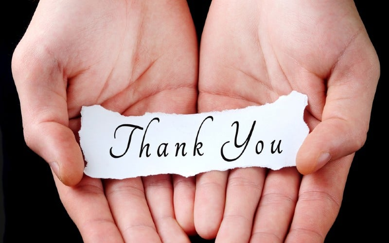 Hands honding paper with thank you message