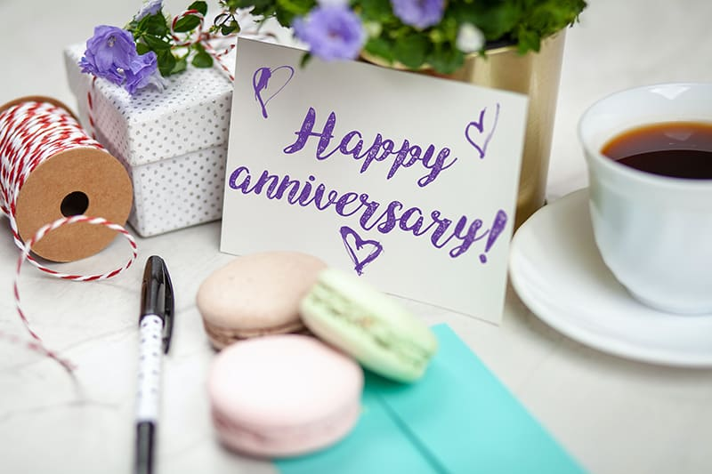 happy anniversary signage on table beside coffee