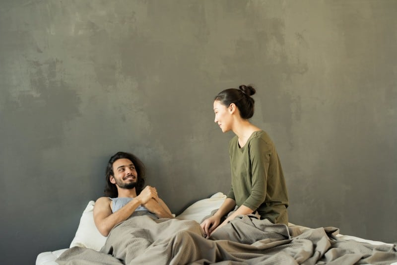 smiling man looking at woman in bed