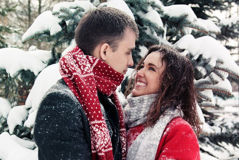 happy couple in snow smiling at each other