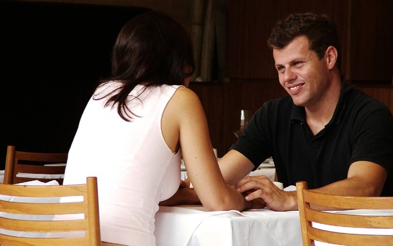 happy man and woman sitting at a restaurant table