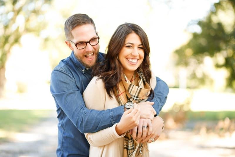 happy man embracing a woman both facing same direction