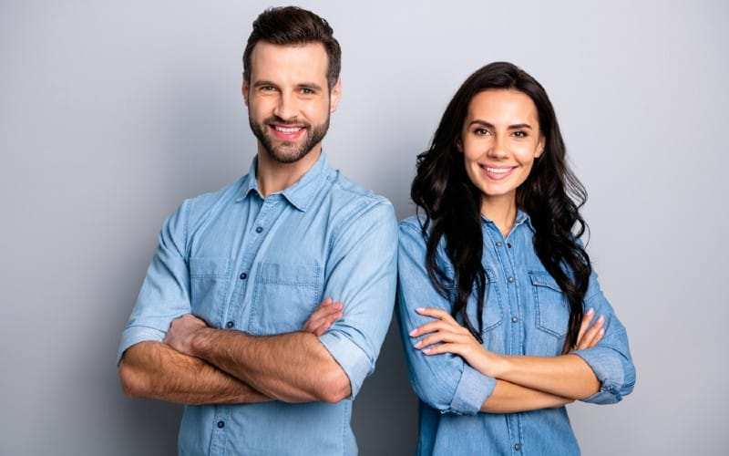 Happy man standing beside happy woman both wearing blue tops