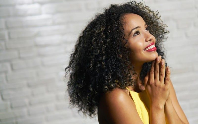 Happy praying beautiful african american woman